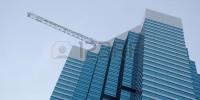 2481326-un-rascacielos-con-la-construccion-de-vidrio-tintado-azul-en-el-primer-plano-una-grua-en-el-fondo